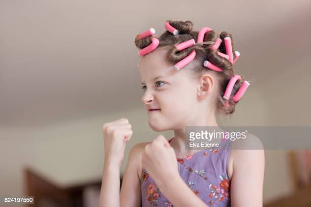 Grimacing girl in pink hair rollers with fists raised
