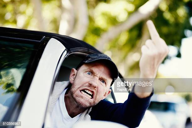 Grimacing male driver makes obscene gesture at someone