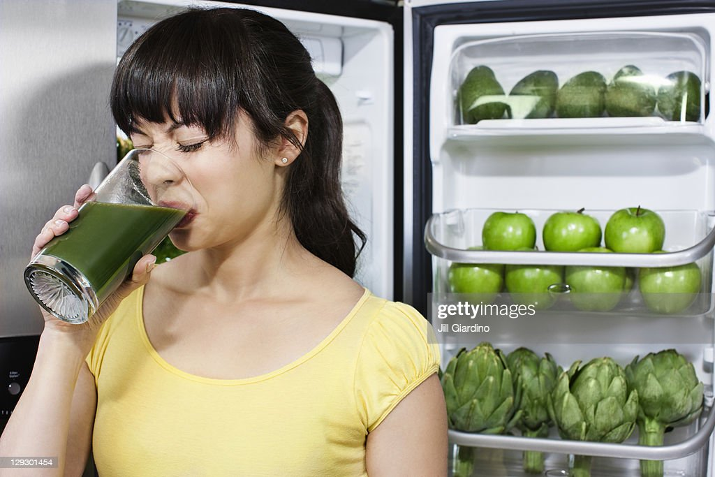 Grimacing mixed race woman drinking healthy drink near refrigerator : Stock Photo