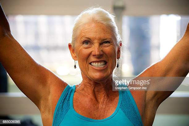 Grimacing older woman working out in gymnasium