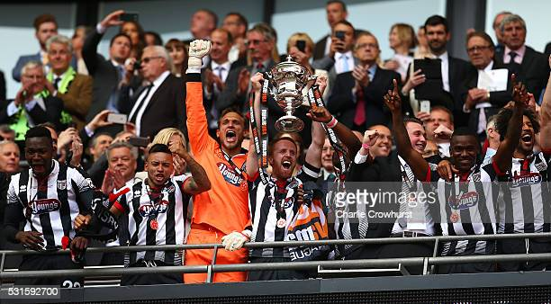 Grimsby's Craig Disley lifts the trophy as he celebrates the teams win and promotion to the football league during the Vanarama Football Conference...