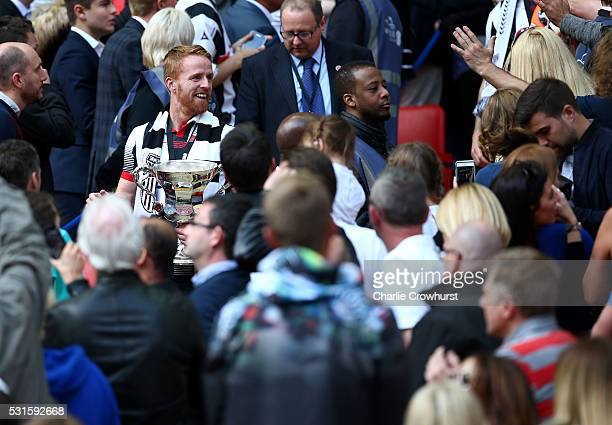 Grimsby's Craig Disley walks down to the pitch with the trophy as he celebrates the teams win and promotion to the football league during the...