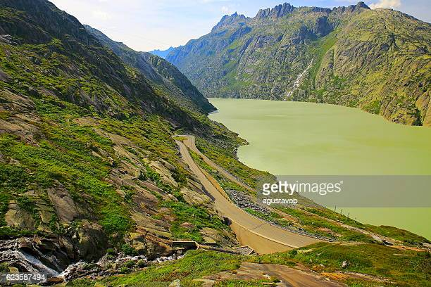 Grimsel pass landscape, glacier lake reservoir, Road crossing swiss alps