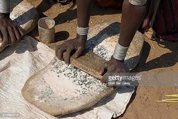 Grind seeds to make injera at Daasanech village