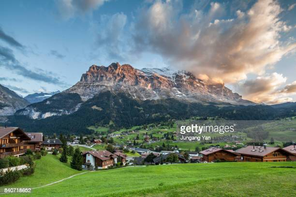 grindelwald village by bernese oberland against sky at swiss alps - ベルンカントン ストックフォトと画像