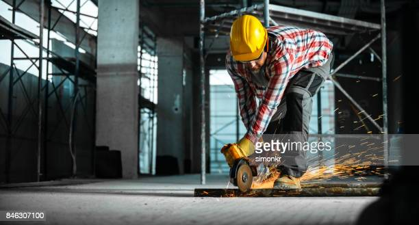 grinder being used to cut through metal pipe on floor - trousers stock pictures, royalty-free photos & images