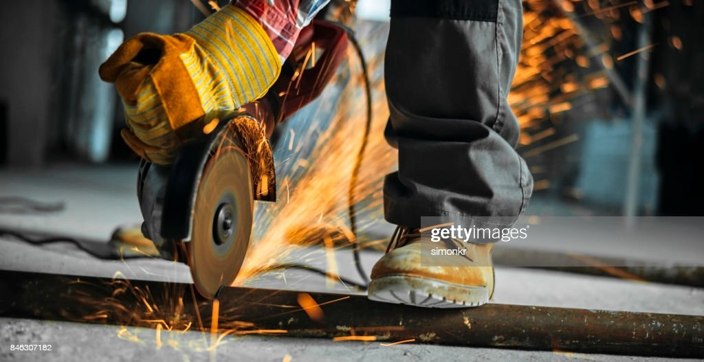Grinder being used to cut through metal pipe on floor : Stock Photo