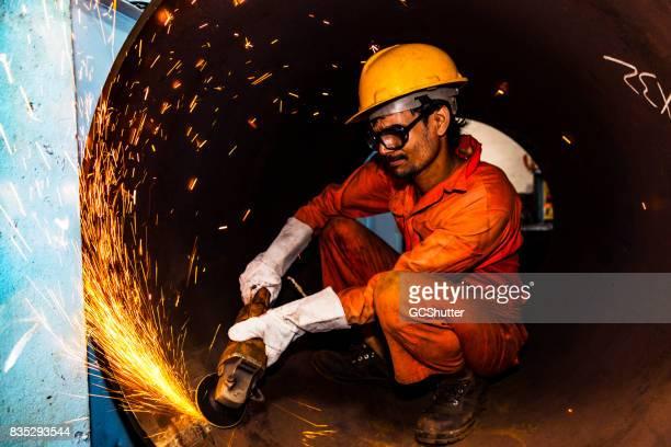 Grinder försiktigt mjuka insidan ytan av ett metallrör