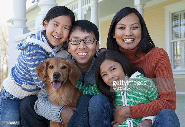 Grinning Asian family sitting together with dog