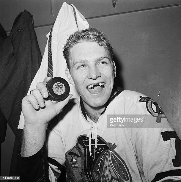 A grinning Bobby Hull forward for the Chicago Blackhawks holds up a puck in the locker room following a game against the New York Rangers at Madison...