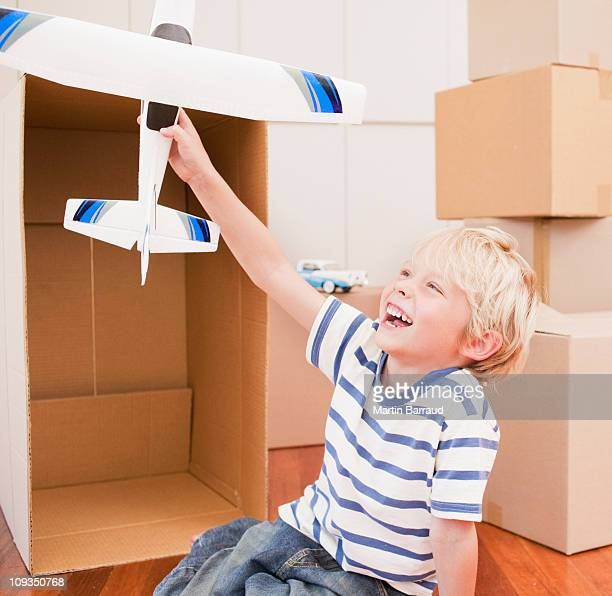 Grinning boy playing with model airplane in his new house