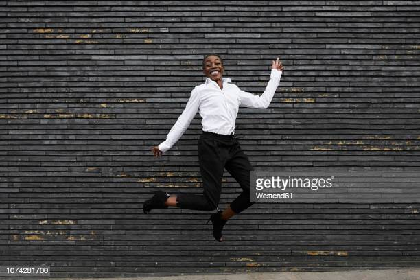 Grinning businesswoman jumpng in the air