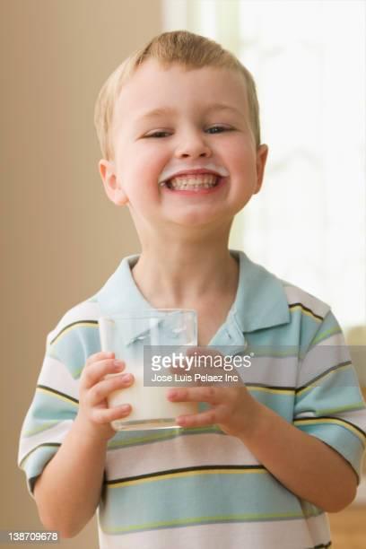 Grinning Caucasian boy drinking milk