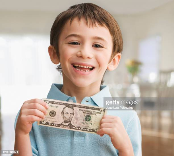 Grinning Caucasian boy holding five dollar bill