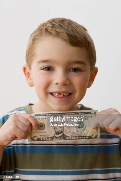 grinning caucasian boy holding five dollar bill - tooth fairy stock pictures, royalty-free photos & images