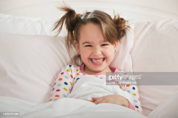 grinning caucasian girl laying in bed - west new york new jersey - fotografias e filmes do acervo