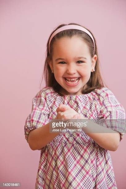 grinning caucasian girl with hands clasped - mani incrociate foto e immagini stock