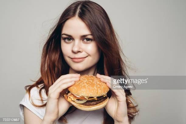 Grinning Caucasian woman holding cheeseburger