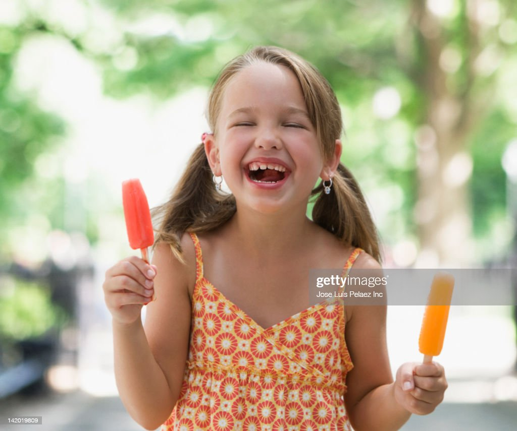 grinning girl holding popsicle picture id142019809