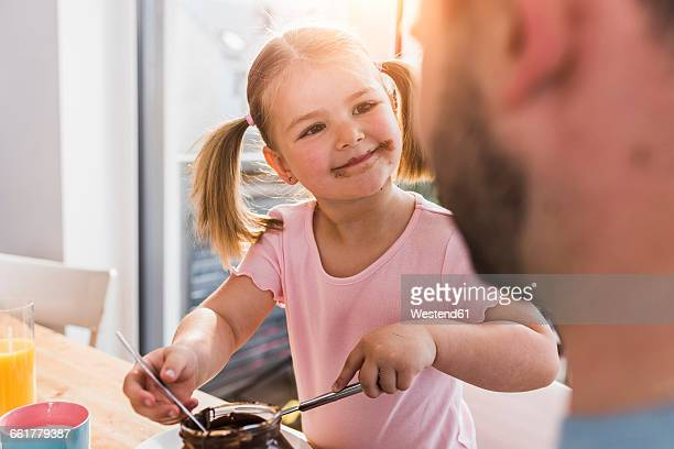 Grinning girl with smeared mouth looking at father