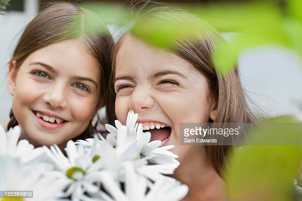 Grinning girls holding flowers