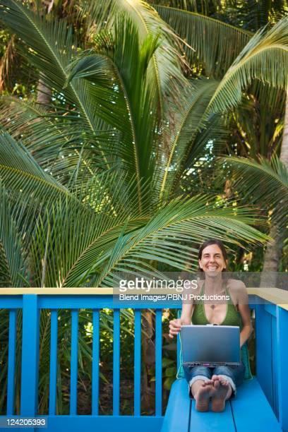 grinning hispanic woman using laptop on deck - パホア ストックフォトと画像