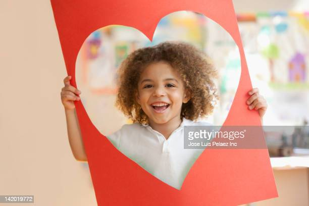 grinning mixed race boy looking through heart-shaped hole - valentines african american stock pictures, royalty-free photos & images