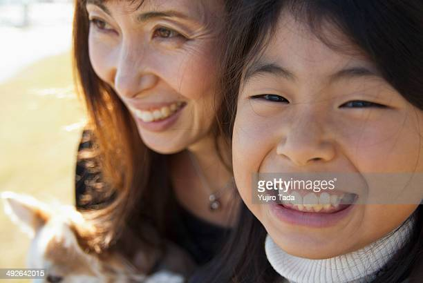 A grinning mother and daughter with dog, close-up