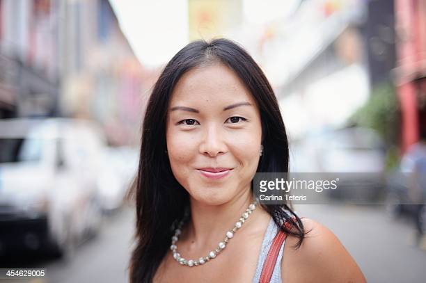 grinning portrait of an asian woman on the street - ビーズ ストックフォトと画像