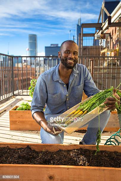 Grinning Urban Gardener with Tray of Produce