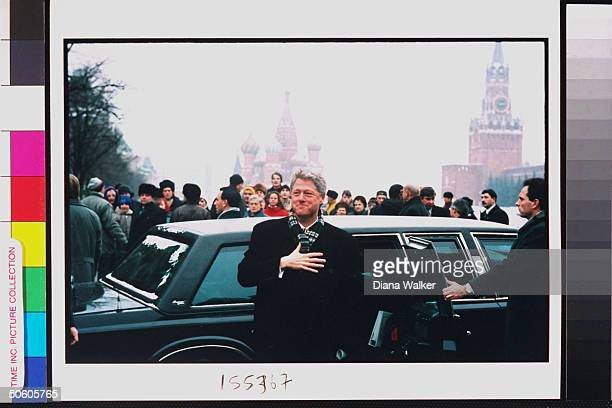 Grinning US Pres. Bill Clinton standing in front of his limo, secret serviceman at his side, curious crowd beyond, in Red Square during summit.
