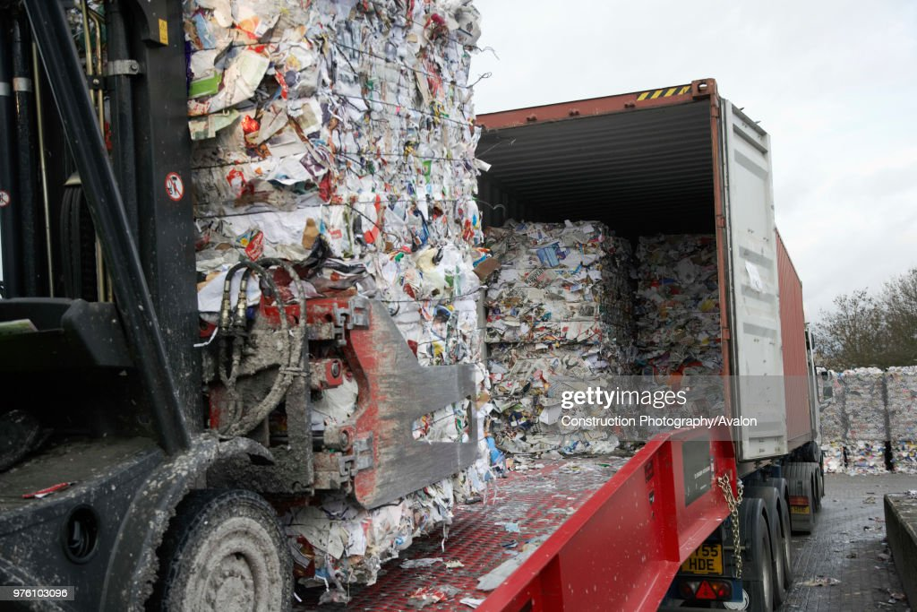 Grip lift truck carrying compacted recycling on to truck : News Photo