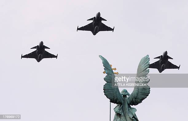 Gripen JAS39 type aircrafts of the Hungarian Air Force fly over the statue of the Gabriel archangel to honour new officers of the Hungarian Army who...