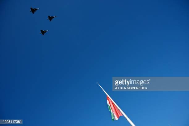 Gripen type aircrafts of the Hungarian Air forces fly over a national flag in front of the parliament during a ceremony marking the national day on...