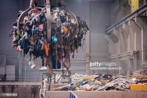 A gripper holds garbage that is ready to be deployed on a roller convey and headed to the incinerator's oven after being mixed at the waste...