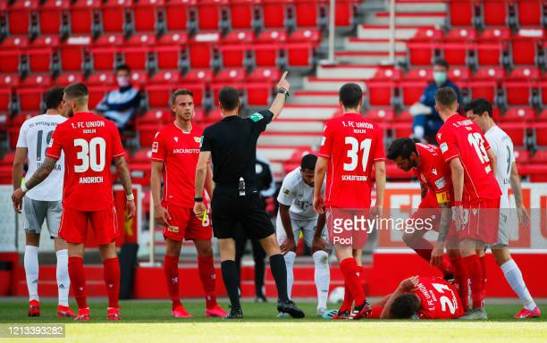 Grischa Promel of Union Berlin reacts after sustaining an injury as referee Bastian Dankert speaks with FC Union Berlin's Marcus Ingvartsen during...