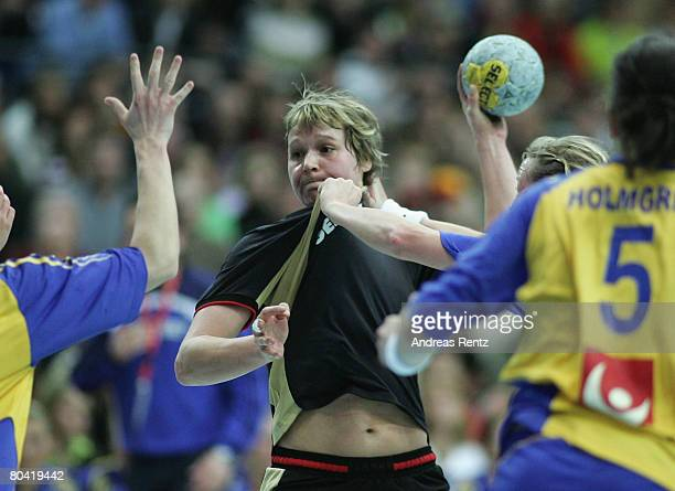 Grit Jurack of Germany is challenged by Sweden's defense during the women's handball Olympic qualification tournament match between Germany and...