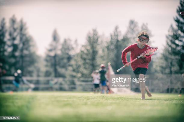 gritty little girl playing lacrosse - lacrosse stock pictures, royalty-free photos & images