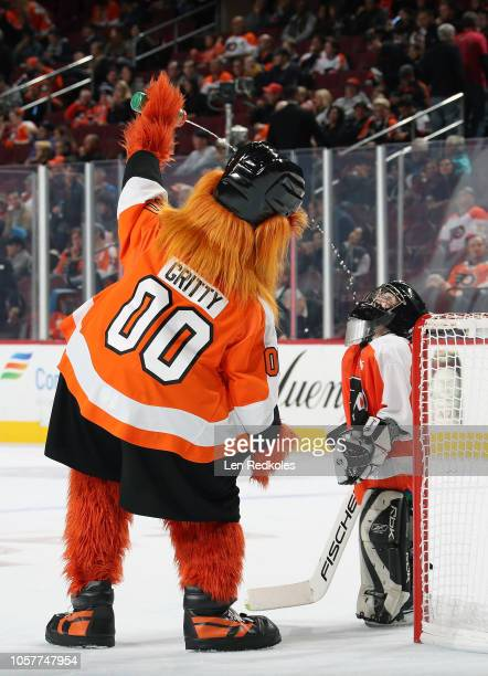 Gritty the mascot of the Philadelphia Flyers gives a drink of water to a member of the mites on ice during the second period intermission against the...