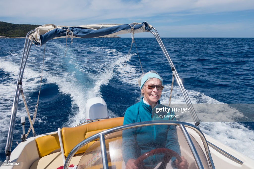 Senior woman steering a speedboat in Greece like a boss. Enjoying herself and smiling radiantly. Overall blue color palette.