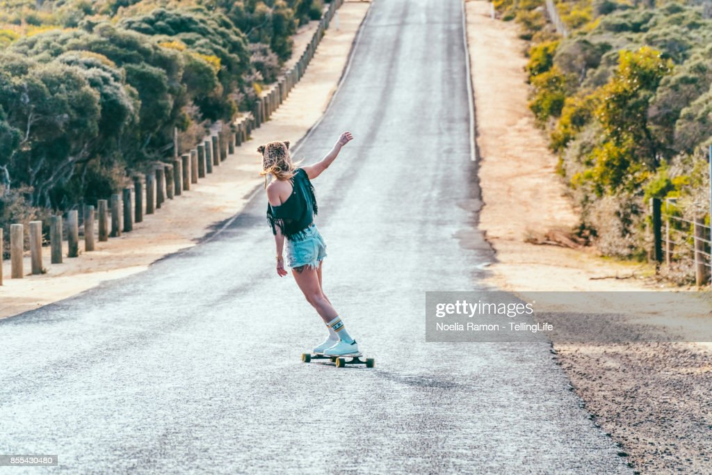 Gritty Women: woman with a longboard skate : Stock-Foto