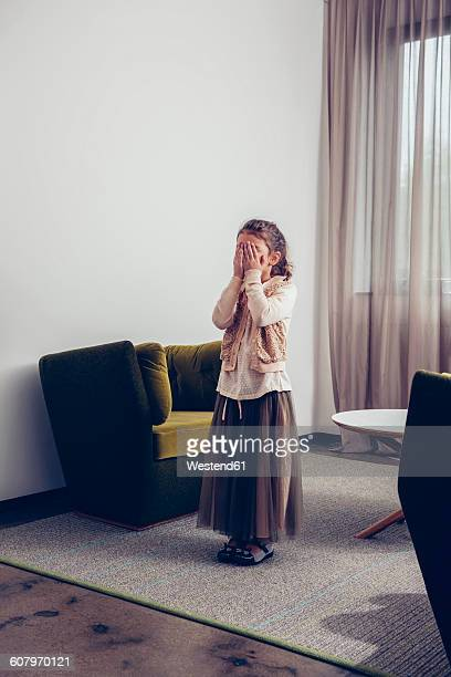 grl covering her face with her hands while standing in living room - see no evil hear no evil speak no evil stock pictures, royalty-free photos & images