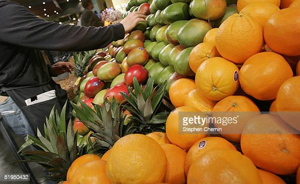 A grocer arranges mangoes in the produce section at Whole Foods January 13 2005 in New York City New eating guidelines issued by the US government...