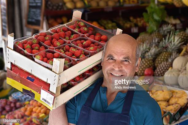 grocer carrying a box of strawberries - market vendor stock pictures, royalty-free photos & images