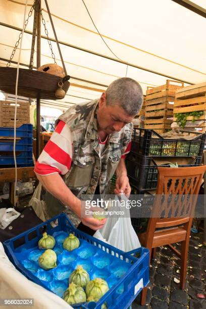 a grocer picks up zucchini in the flower market in rome. - emreturanphoto stock pictures, royalty-free photos & images
