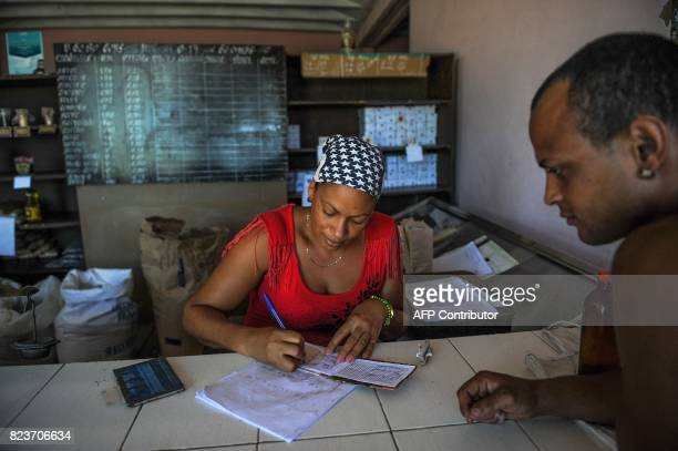 A grocer writes on a ration book in San Luis Santiago de Cuba province on June 20 2017 Each Cuban home receives certain basic foods every month for a...