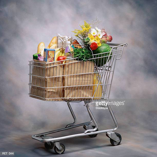 groceries and flowers in shopping cart - caddie rempli photos et images de collection