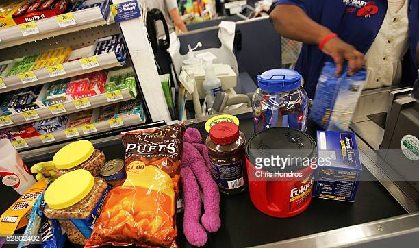 Groceries and other retail items move down the checkout counter of a WalMart Supercenter May 11 2005 in Troy Ohio WalMart America's largest retailer...