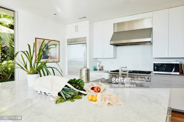 groceries in canvas bag on kitchen counter in home - kitchen worktop stock pictures, royalty-free photos & images
