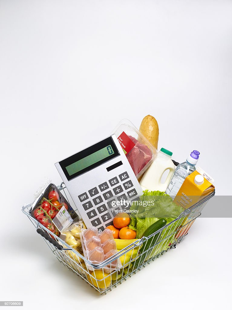 groceries in supermarket basket with calculator stock photo getty